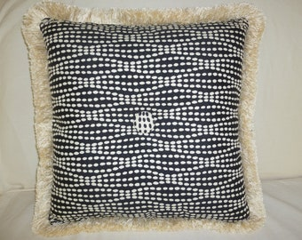 Spotted black and ivory tufted pillow with contrasting button