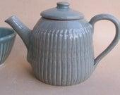 Small stoneware teapot with celadon glaze. Pottery ceramics.