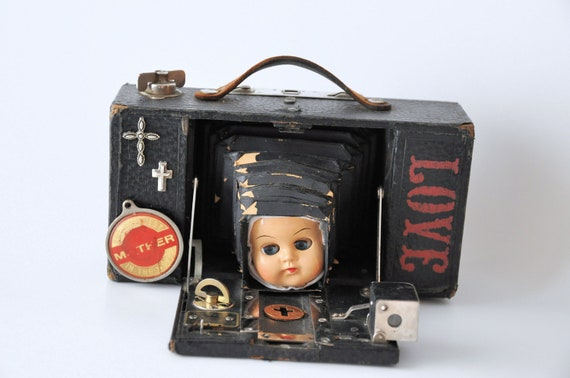 Religious nun doll assemblage art mounted in vintage camera mixed media art