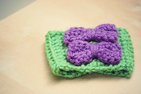 crochet coffee cozy sleeve in green with two purple bows.