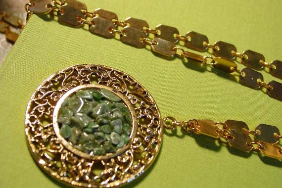 Gold tone necklace pendant with small green rocks