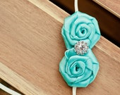 Small Rolled rosettes in Tiffany Blue with a small rhinestone button on a skinny elastic headband/Photoprops/weddings