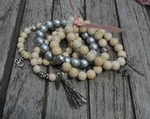 Set of 5 creamy riverstone semi precious stone bracelets adorned with silver charms and silver crystal accents.