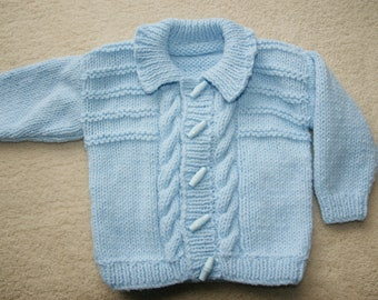 Hand knitted baby aran cardigan with cable design in pastel blue