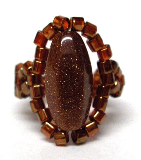 Beaded handmade ring orange bronze color with a goldstone stone in the middle on a stretchy cord