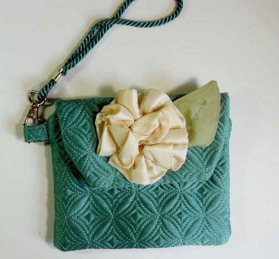 Small teal wristlet or clutch with cream color flower.