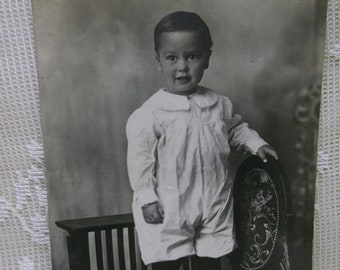 Real Photo Postcard of Cute Little Boy in White Romper standing on Very Ornate Chair - early 1900's