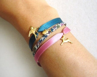 Woodland Bracelet with a tiny acorn, bird and deer on three pink and blue ribbons