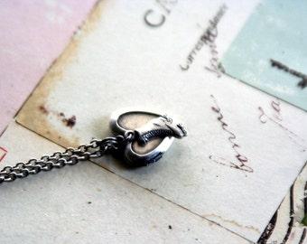 roller skate. locket necklace. silver ox