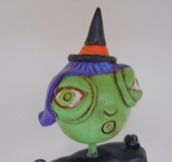 Halloween Witch in White Black Orange Purple and Green with a Skeleton Bucket