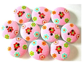 10 Wood buttons 15mm flower picture in asotred colors on pink surface