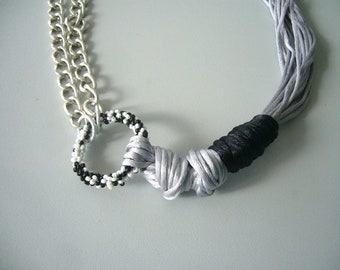 grey necklace with black and metal