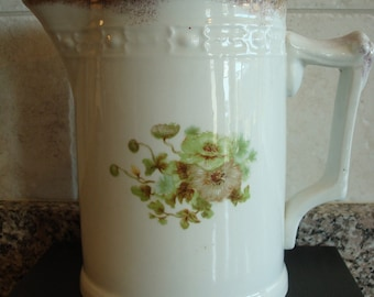 Vintage milk pitcher with green floral design and gold trim