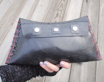 Rubber tire clutch handbag with red stitching, stars on seam and metal snap details.