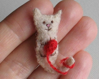 Cat miniature plush felt toy with tiny ball of red yarn