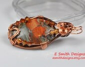 Large fire jasper pendant wrapped in copper wire with copper colored crystal