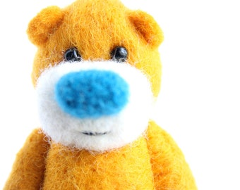 Miniature orange pocket bear with a bright blue nose