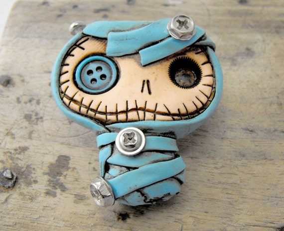Crazy baby mummy brooch in dirty blue. Mechanical look. Real screws fixed in his body and one button in his eye. Cute baby Frankenstein