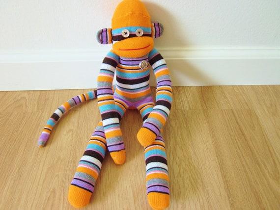 Orange striped sock monkey plush - with purple, pink, black, gray, white, and blue stripes
