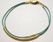 Minimalist gold tube stacking bracelet in teal