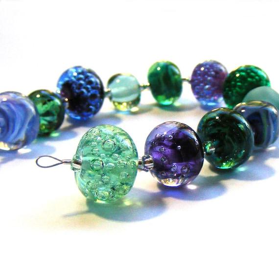 Handmade lampwork glass bead set of multicoloured 12 renegade beads - predominantly green and purple lampwork orphan beads