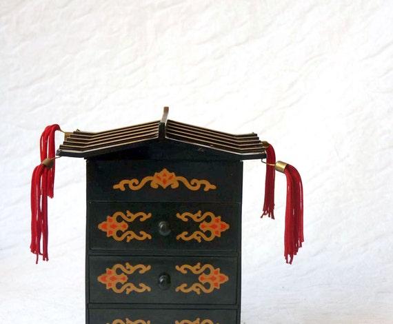 Pagoda jewel box, black plastic with floral motif, gilt accents, red silk tassels