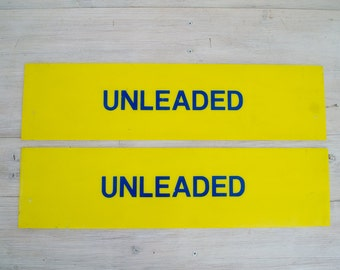 vintage yellow and navy blue unleaded petrol signs