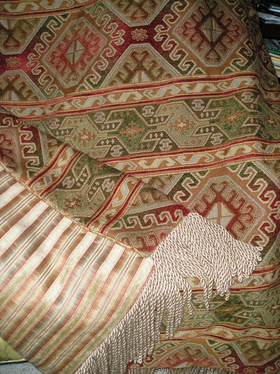 Throw Blanket in Earth Shades of Red with Brown tones, Green, and Bronze, and Features a Stripe Reverse Side