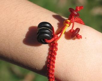 Slender knotted bracelet in red and saffron
