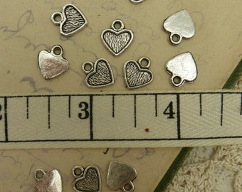 20 tiny shallow bezel heart charms in antique silver tone size 11 mm long by 10 mm wide suitable glue on