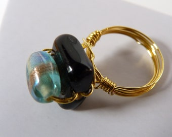 Wire wrapped, size 6 ring with two hand made glass beads.