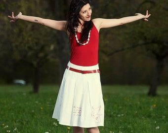 Skirt with hand-embroidered motif and red leather belt, white cotton