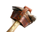 Leather hammer holster with security strap.