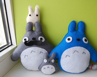 Totoro plushies family. Grey Totoro with moustache, blue Totoro with a bundle and 2 mini Totoro