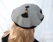 Black and beige beret, hat, cap, bottom soft cotton jersey, top padded wool with button and tassel, gold
