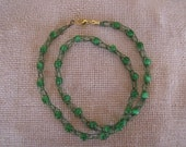 Kelly green knit wire necklace with cats eye green beads. 22 inch length.