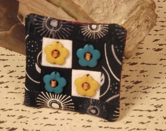 Black and white beaded pin brooch.  Flowers in teal and yellow.