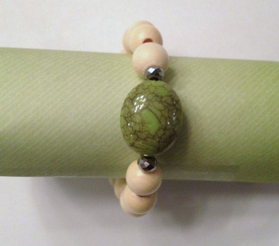 Creme beaded bracelet with green center stone
