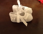 Booties with white flowers, lace, and bows.
