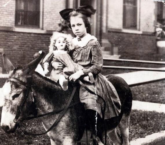 vintage photo Girl on Donkey Holds Doll RPPC