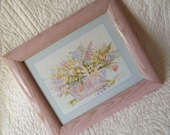vintage 1980s picture of a basket of flowers framed in a pink wood frame