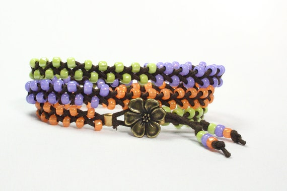 Braided wrap bracelet.  Lavender, lime green, orange tangerine seed beads.  Antique gold flower button.  Bright colors.  Hippie.