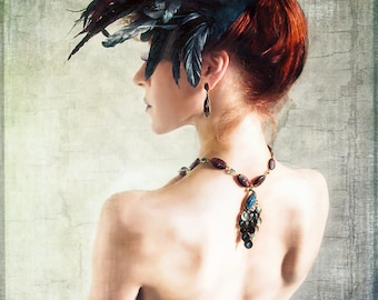Madame Peacock is a fashion portrait of a woman with her head adorned with a peacock style feather headpiece and wearing a peacock necklace