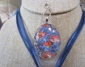 Stunning homegrown pressed apricot Verbena and Periwinkle Forget Me Nots behing handcut crystal clear oval pendant.