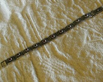 Vintage sterling panel link bracelet with bezel set garnets and marcasites.