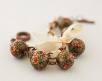 Beads with Flowers on the Golden Marble Background and Cream Ribbon Bracelet