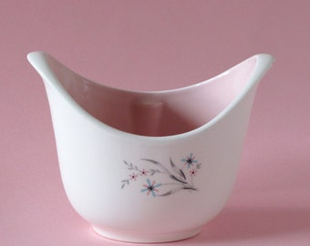 Sugar bowl with pink glaze inside and pink and blue flowers with gray leaves without the lid may be by Taylor Smith Taylor