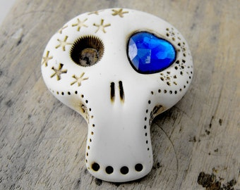 White sugar skull with a deep blue shiny heart inside his eye. Brooch, keychain, pendant or magnet (you choose)