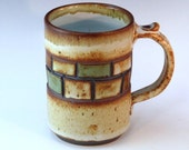 Beautiful mug with colored squares and textured handle with thumb rest.