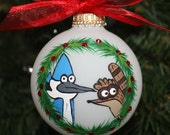 Handpainted Glass Personalized Ornament with the Regular Shows Mordecai and Rigby peeking through a Christmas wreath